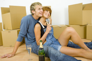 Young couple sitting on the floor in flat. They're looking happy. Celebrating removal with champagne